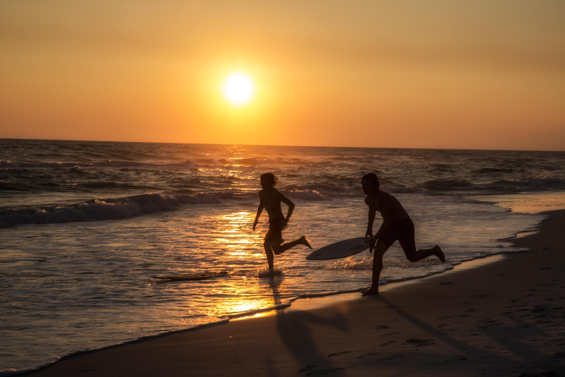 Lifestyle Photographer | Boys Running On Beach With Surf Boards